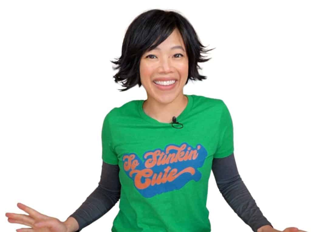 A woman with short black hair wearing a green tee shirt that says 'so stinkin' cute'.